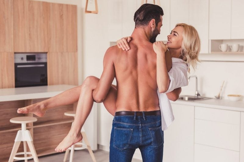 Beautiful young couple is having fun in kitchen at home.