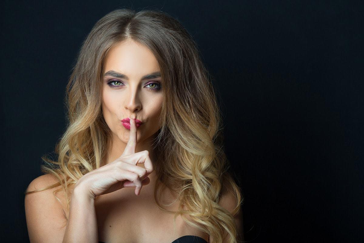 Sensual blonde woman making shh