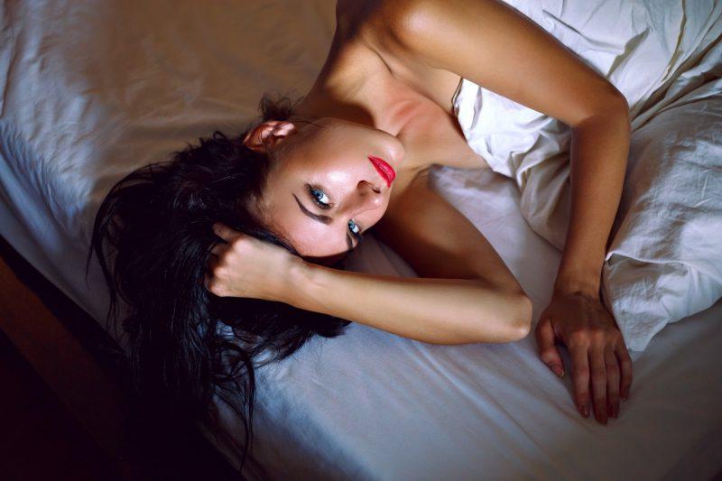 Sensual elegant woman brunette with long hair in bed