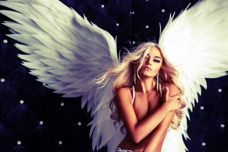 Gorgeous blonde woman with angel wings: the goddess of feminized society
