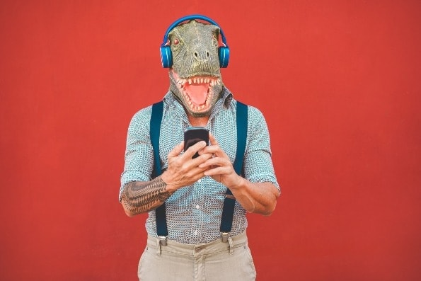 Tattooed old man with t rex head using smartphone