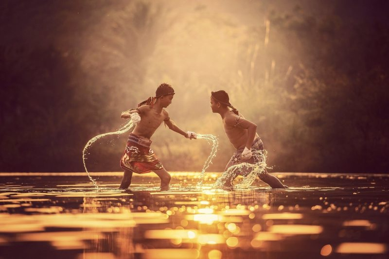 Two asian boys fighting in the water
