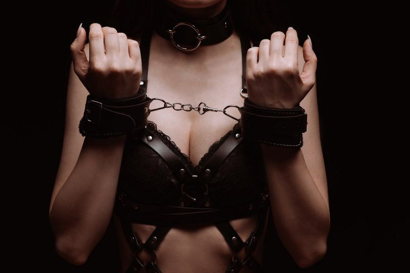 Woman in leather being handcuffed bdsm