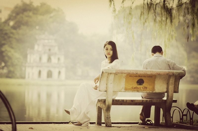 A woman sitting at a lake with a sad guy next to her