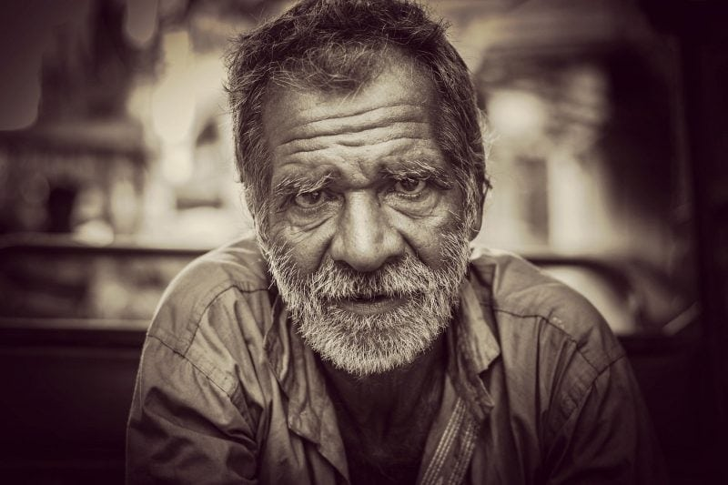 Old man with a beard looking into camera