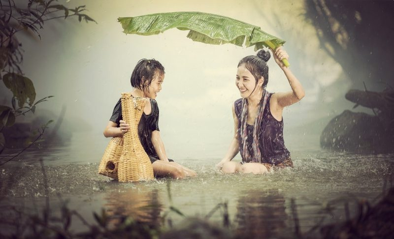 Two asian women being happy in the rain