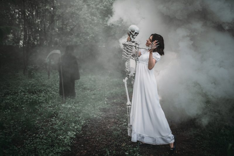 Female succubus in white dress with skeleton