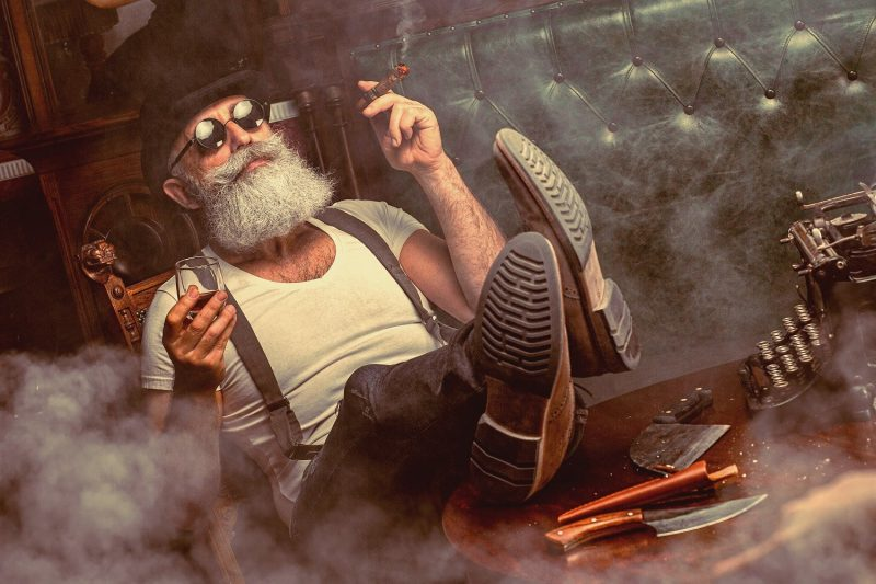 Brutally handsome old man with beard cigar and whiskey truly having outcome independence