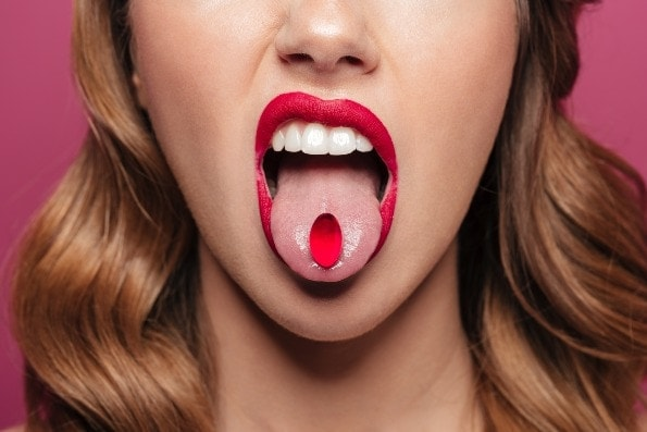 Hot brunette with red pill in mouth