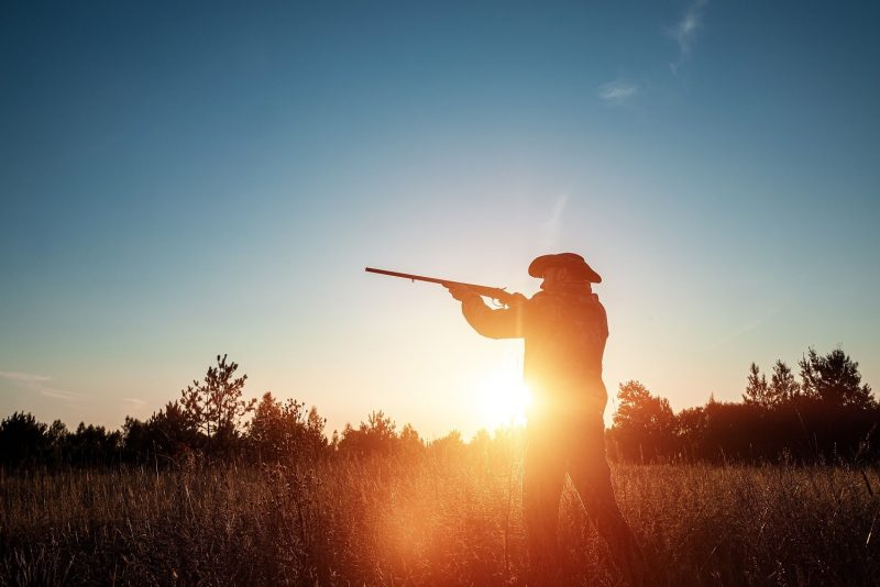 Hunter with hat and rifle in sunlight