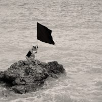 Woman putting a black flag on an island