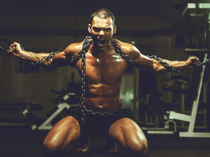 Muscular man in chains breaking free