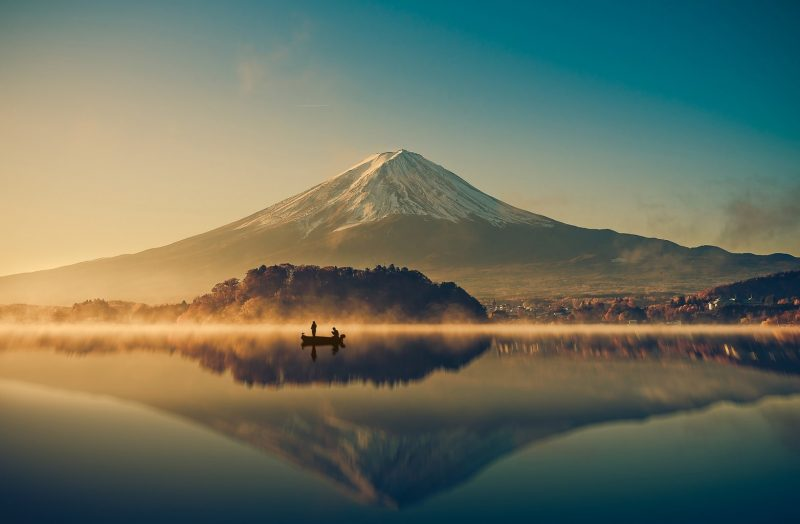 Boat on a silent lake in front of huge mountain