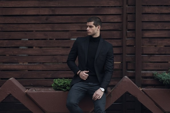 Fashionable man in suit sitting on wooden wall