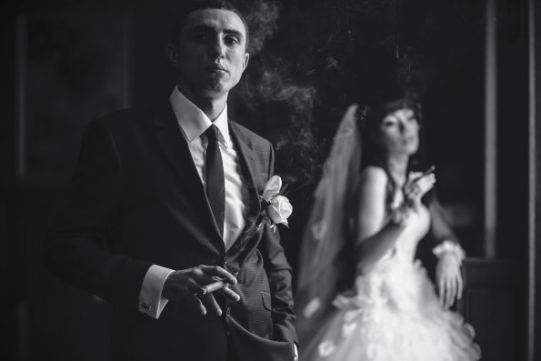Groom smoking cigar with wife in the background