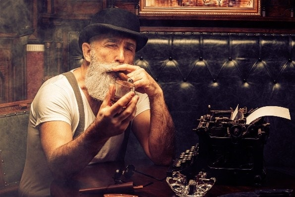 Handsome bearded man smoking cigar drinking whiskey