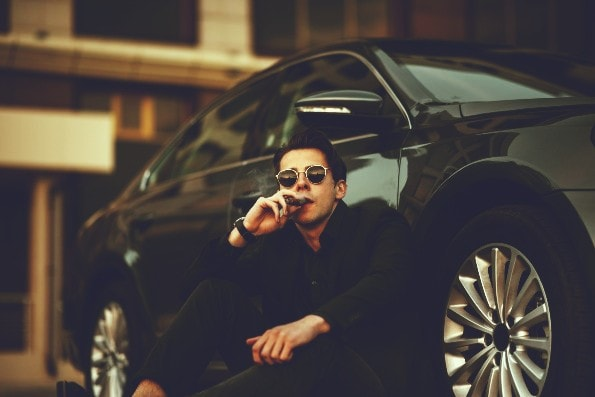 Handsome business man with cigar and expensive car