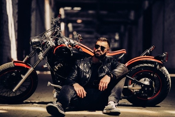Handsome man in leather jacket with motorbike