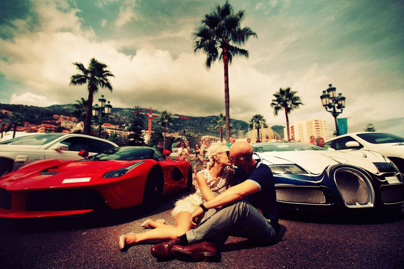 Hot couple sitting in front of ferrair and bugatti wealth