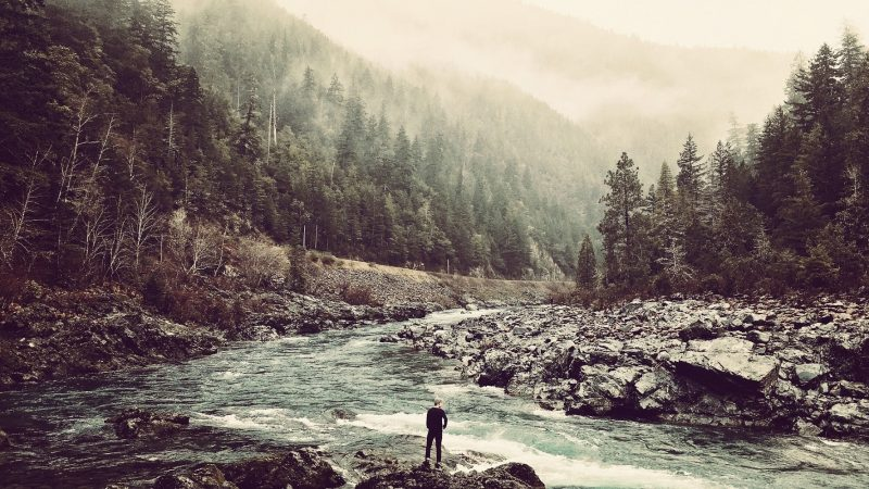 Man standing in a valley at a river with huge mountains
