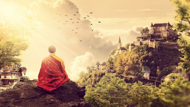Monk meditating on a mountain