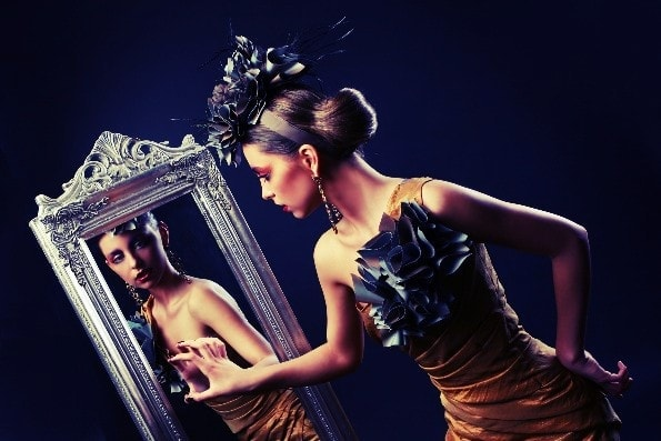 Stylish woman in dress looking into mirror being the male frame