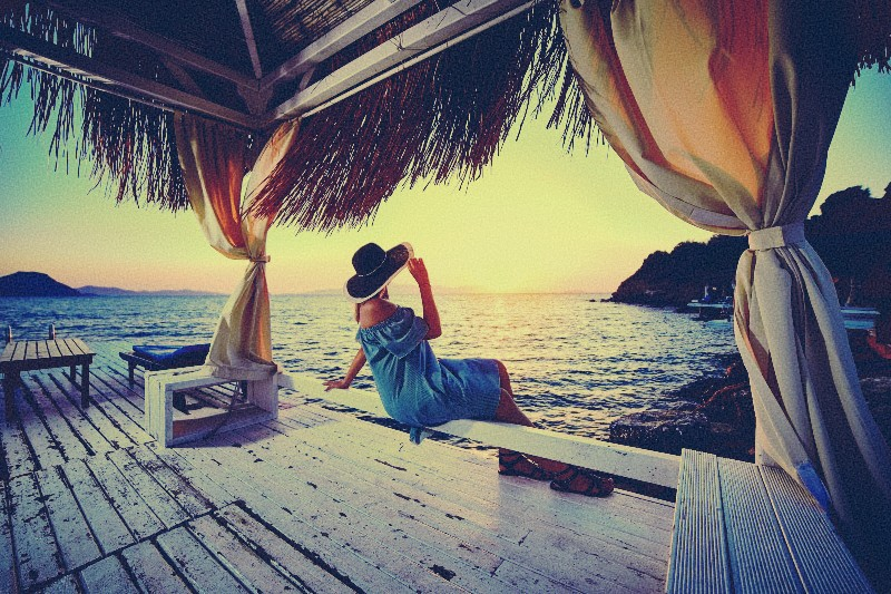 Woman relaxing with hat on expensive vacation sunset