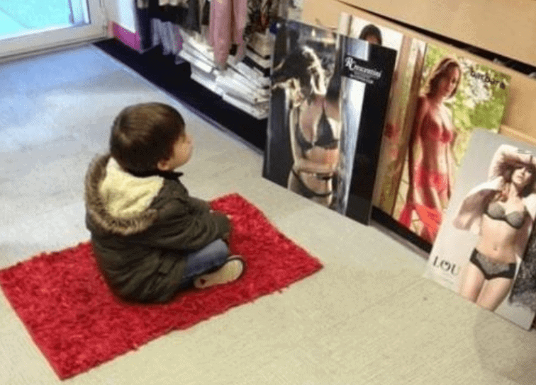 A young boy looking at women in lingerie.