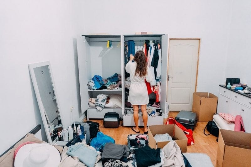 Young woman in cluttered apartment