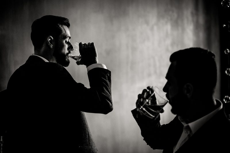 Monochrome view of two men who are drinking alcohol drinks indoo