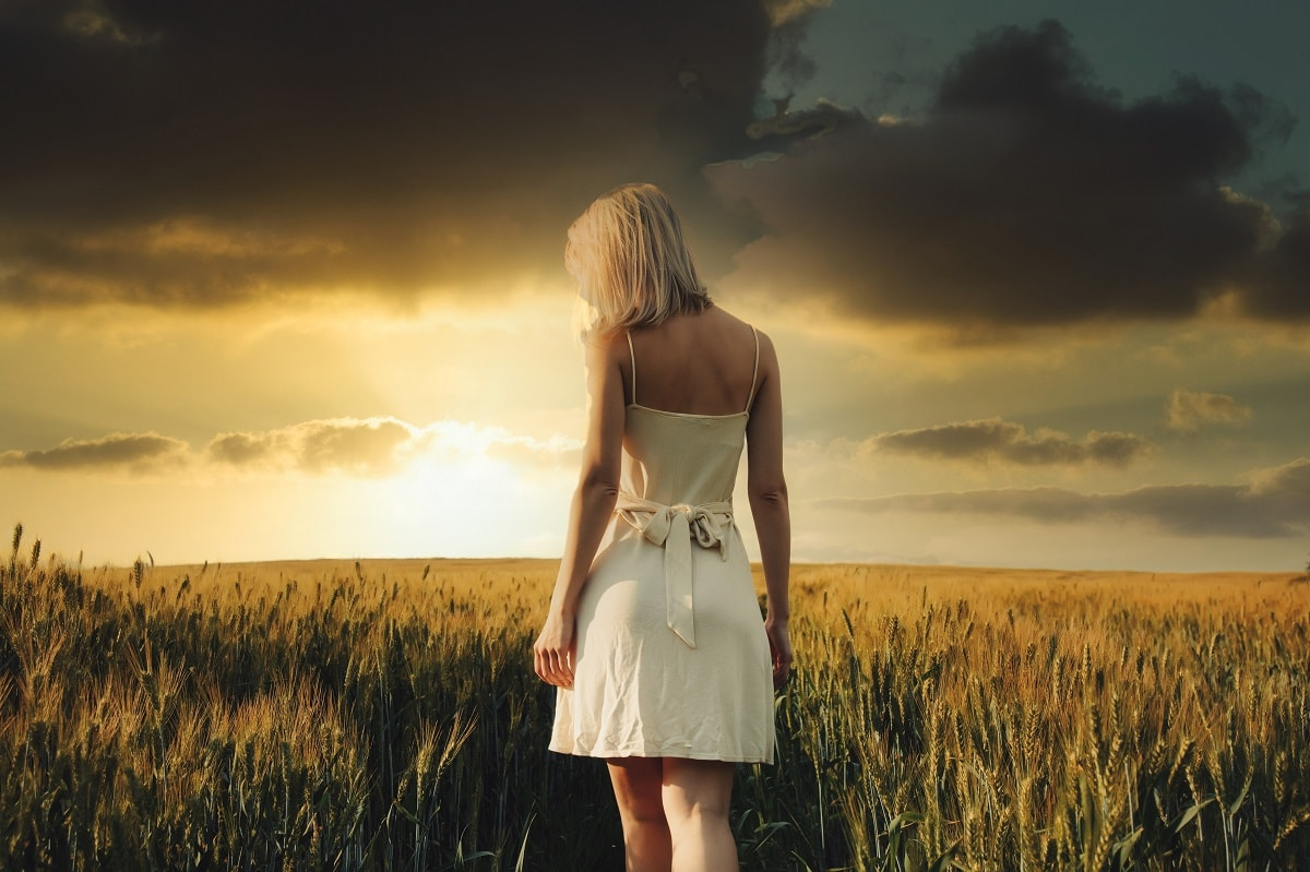 Beautiful blonde girl in wheat field in sunset time