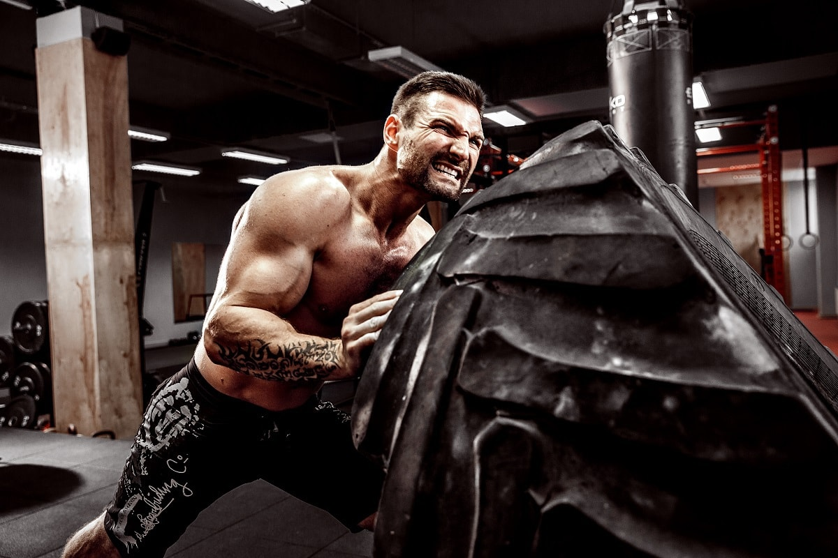 Shirtless man bodybuilder flipping heavy tire due to relentless discipline