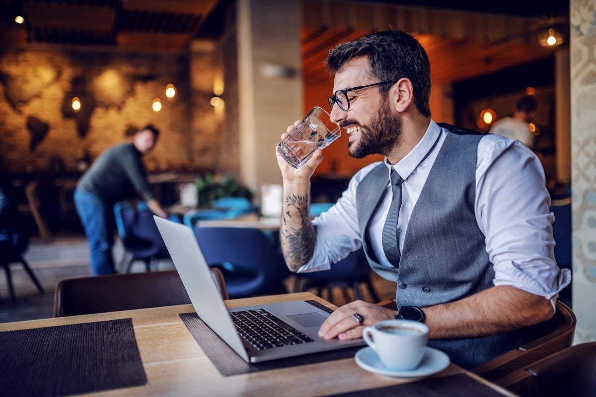 Handsome bearded caucasian businessman in suit and eyeglasses sitting in cafe, using laptop and drinking water.