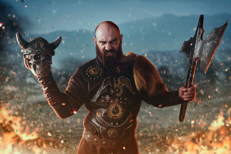 Dark masculinity displayed by a viking man holding axe and a skull
