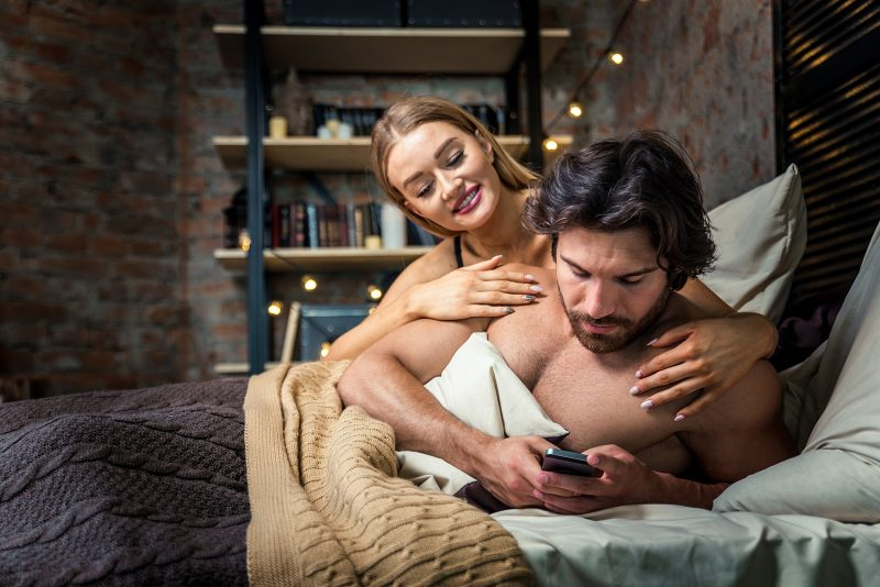 Couple in bed man cheating on phone