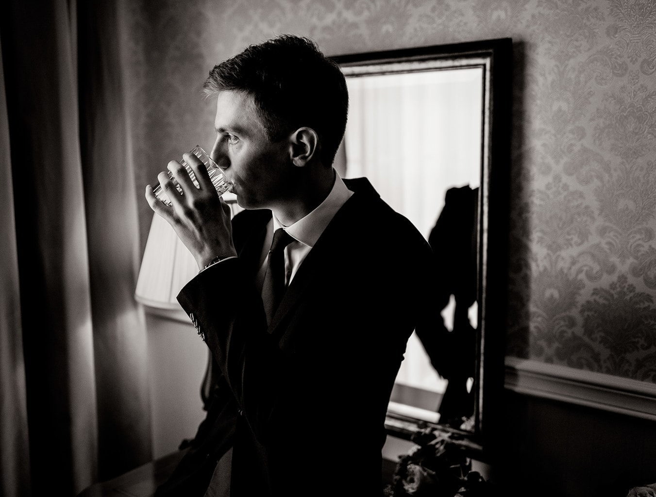 Handsome young man in suit drinking