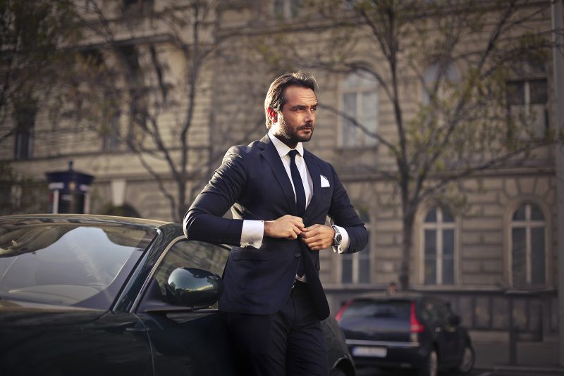 successful man getting out of car